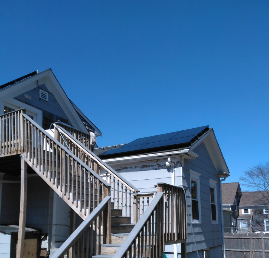 three quarter view of house with solar panels visible on roof